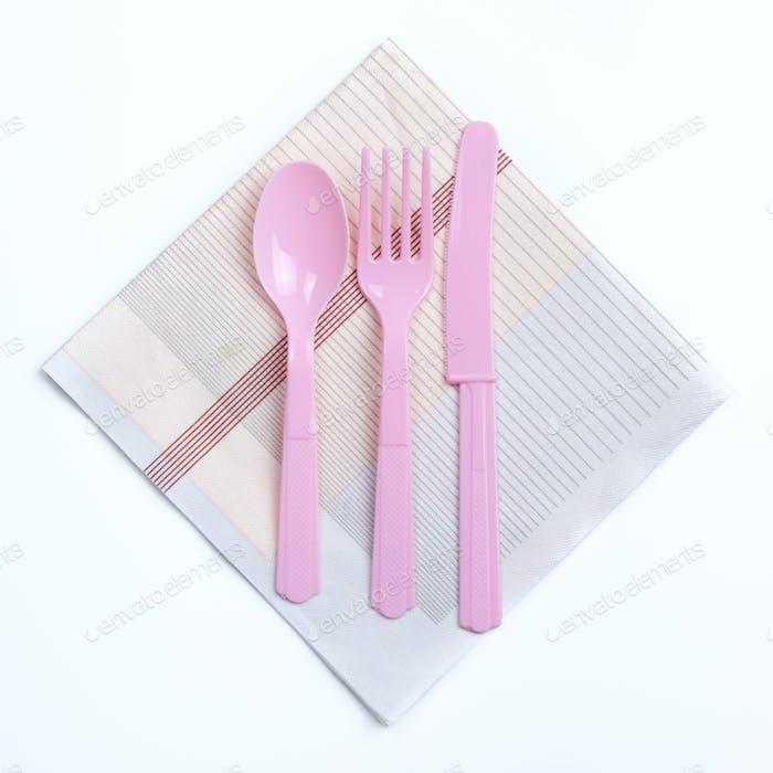Rosa Farbe Kunststoff Gabel, Löffel und Messer auf Serviette