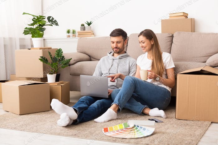 Happy young couple searching samples of interiors on laptop