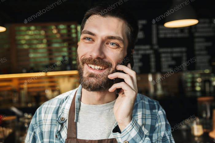 Portrait of joyful barista guy talking on cellphone in street ca