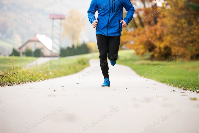 Unrecognizable athlete in autumn park running on concrete path
