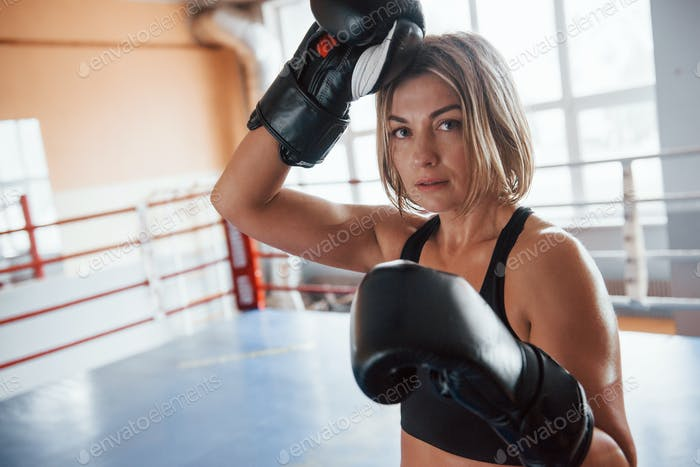 Wipes the sweat from the forehead. Female sportswoman in the boxing ring. In black colored clothes