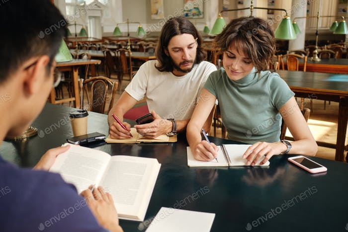 Young attractive students writing notes thoughtfully studying together in library of university