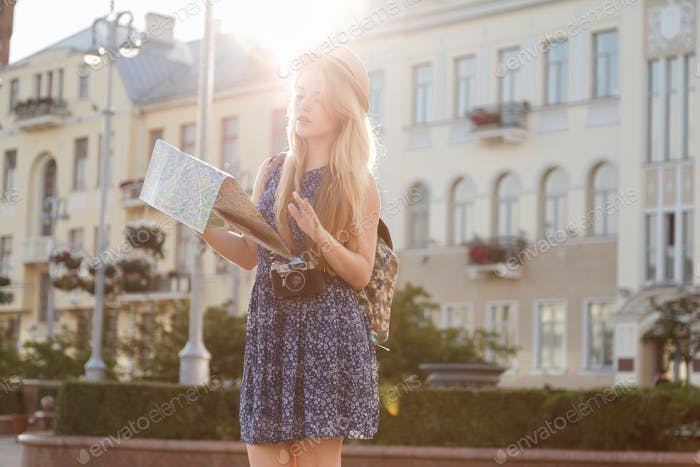 Young woman with city map as tourist