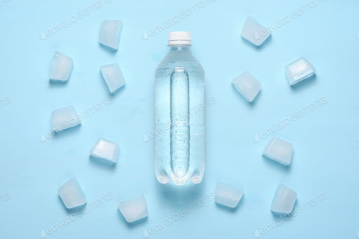 Water bottle and ice pieces on blue table top view