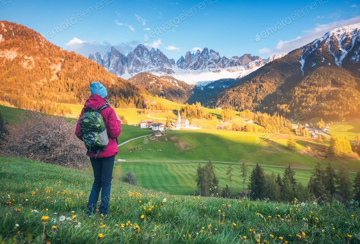 Beautiful young woman with backpack is standing on the hill