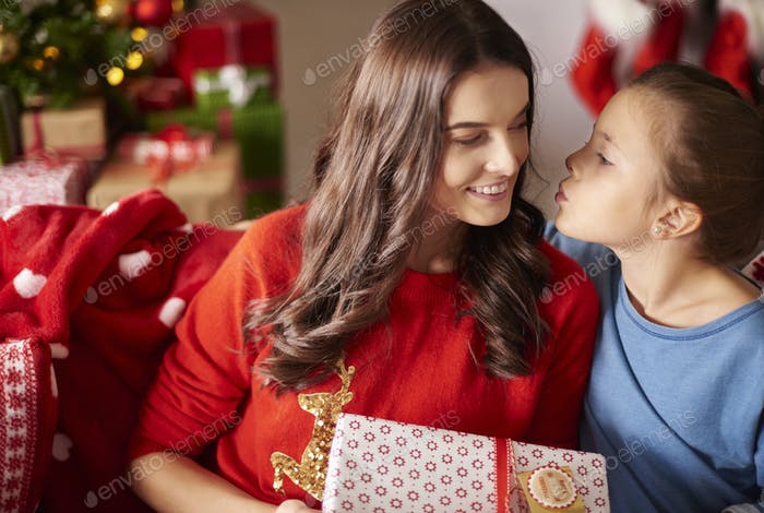 Girl kissing her mom at Christmas