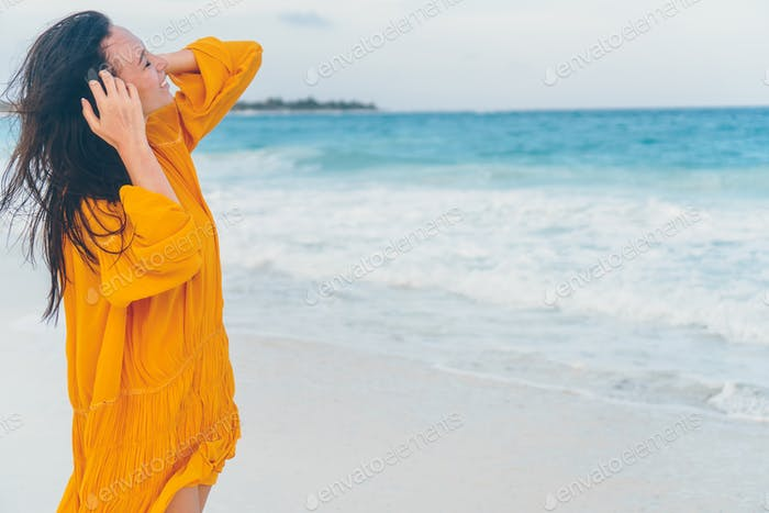 Young beautiful woman on tropical seashore in sunset