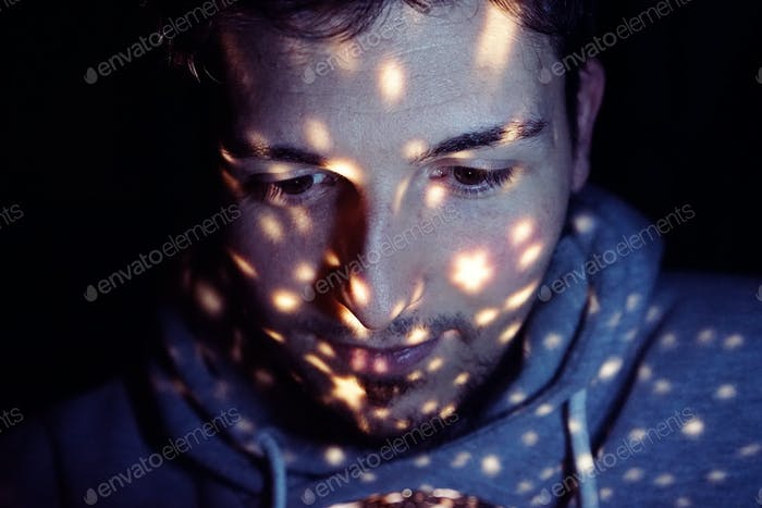 Portrait of a young man with lights in his face