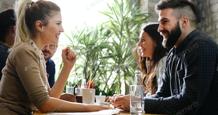 Happy colleagues from work socializing in restaurant