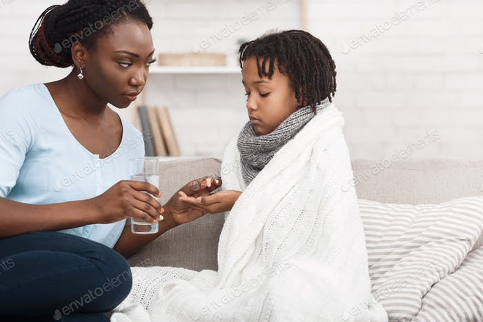 Black mom giving medicine for flu to child