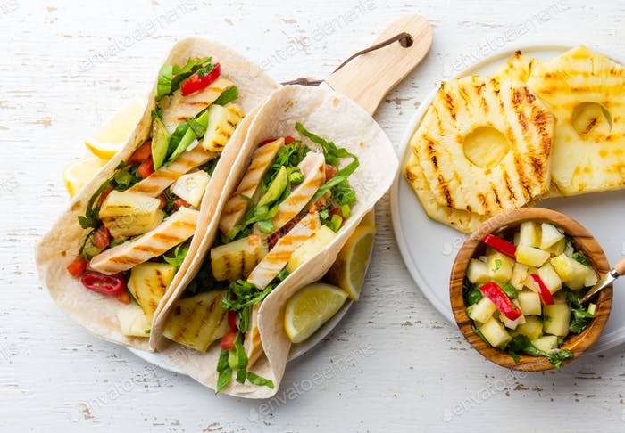 Mexican chicken tacos with grilled pineapple on wooden white background