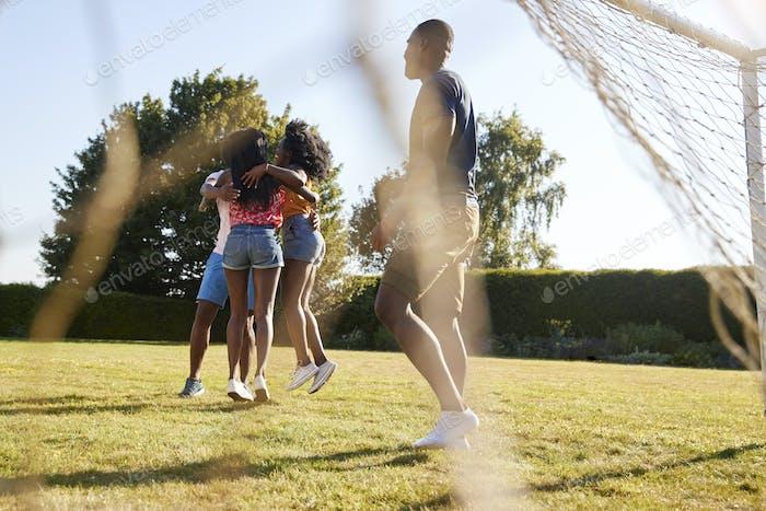 Erwachsene Freunde in einer Feier kuscheln auf Fußballplatz