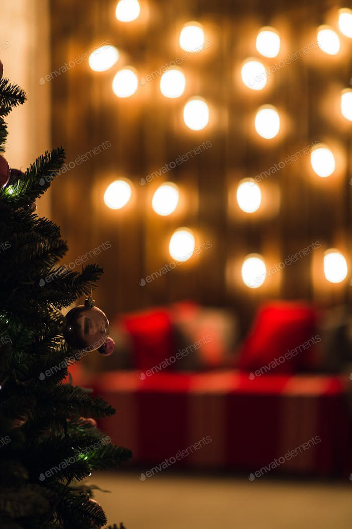 Green New Year tree decorated with ball. Christmas background lights bokeh effect