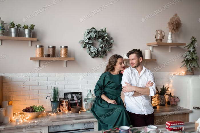 Husband and wife, alike, have fun together in a Scandinavian-style kitchen.