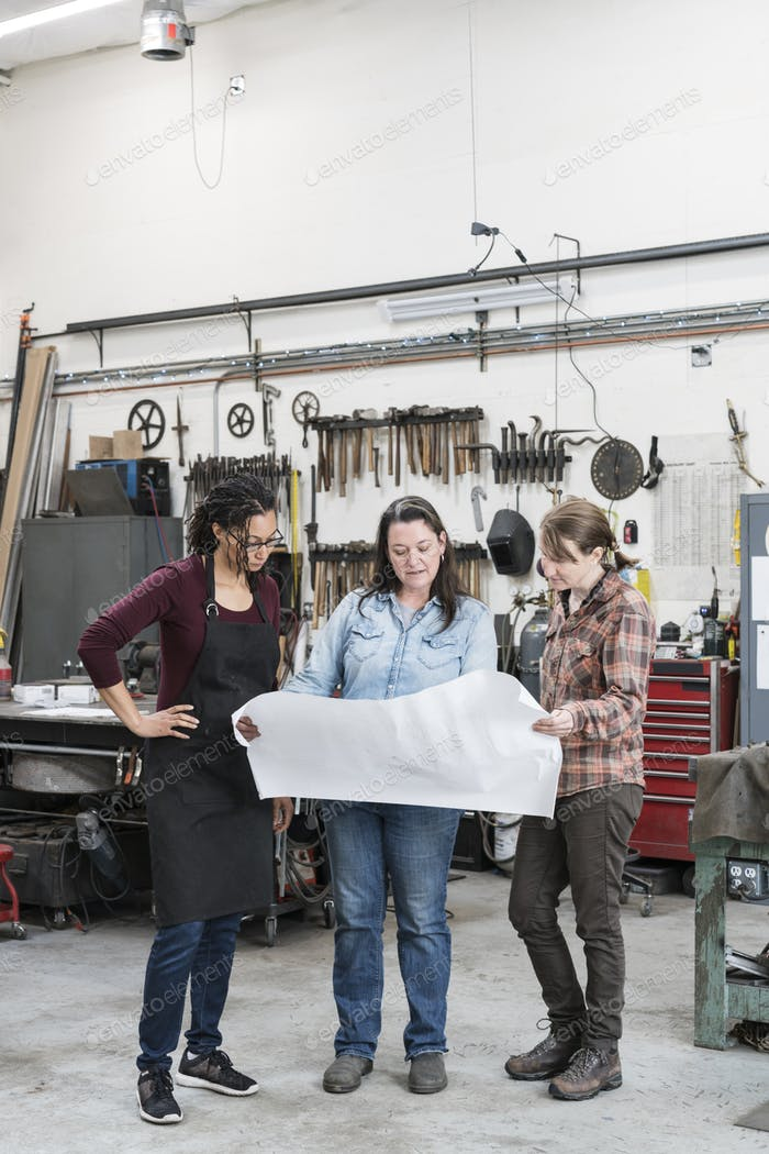 Three women standing in metal workshop, holding technical blueprint.