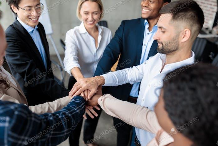 Сотрудники держатся за руки во время Корпоративный встречи по тимбилдингу в офисе