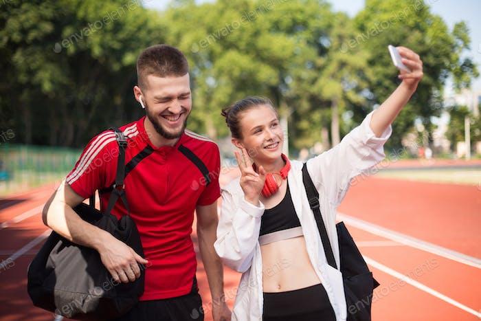 Junge fröhliche Junge und schöne Mädchen glücklich unter Selfie von Handy glücklich auf Stadion