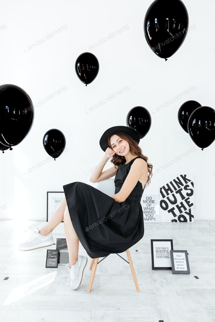 Happy beautiful young woman sitting with posters and black balloons
