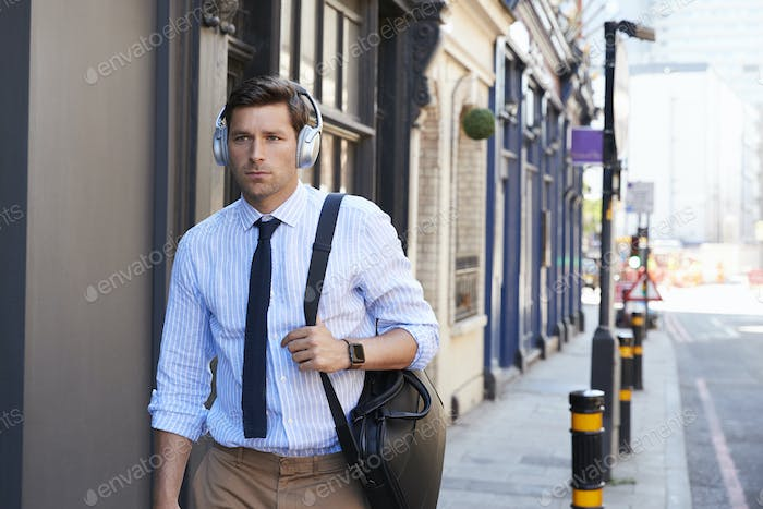 Businessman Wearing Wireless Headphones Walking To Work