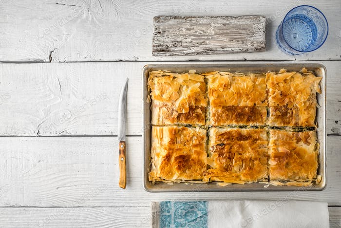Greek pie spanakopita in the metal pan  with table ware horizontal