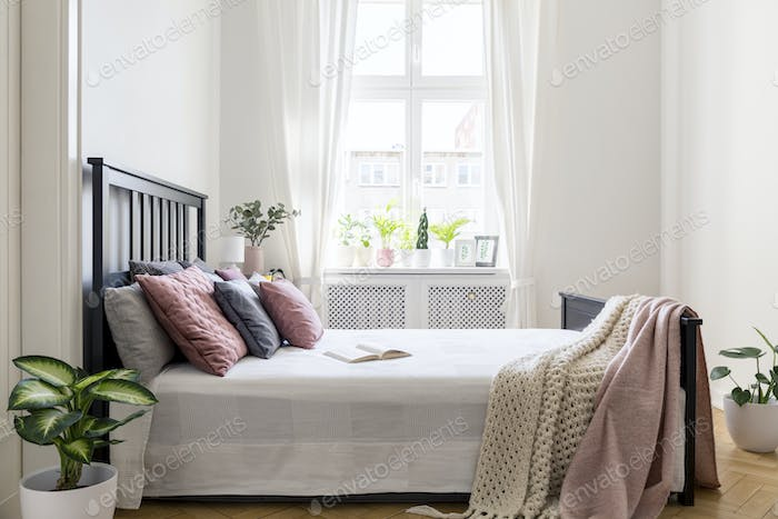 Blanket and pastel cushions on bed with headboard in white bedro