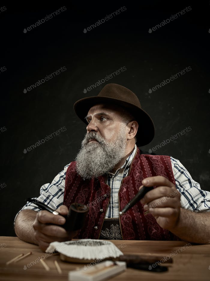 bearded man clogs the tobacco in pipe