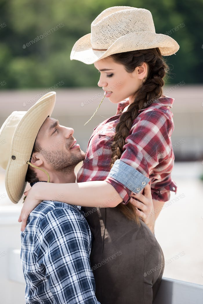 young sensual cowboy style couple hugging with straw