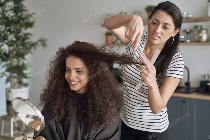 Happy women while trimming their hair at home