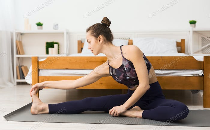 Girl stretching legs in the morning, exercicing yoga at home