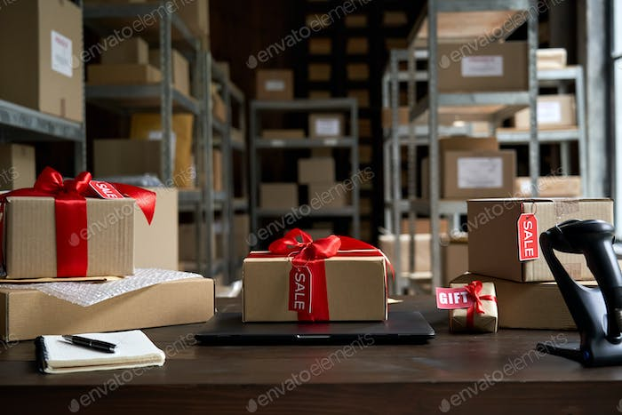 Table with gift parcel boxes on table in warehouse. Online ecommerce sale.