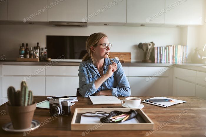 Young female entrepreneur deep in thought while working from home