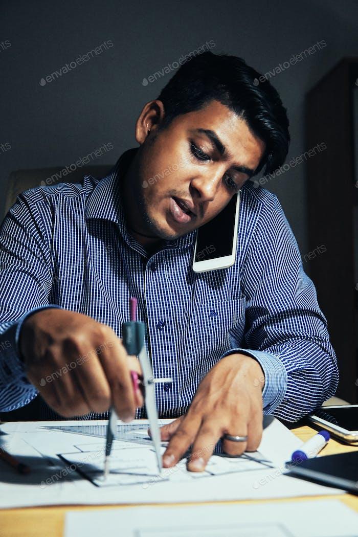 Architect measuring blueprint