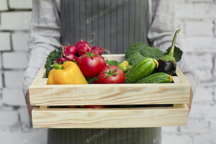 Woman holding big wooden box full of fresh vegetables