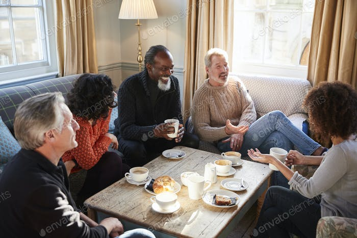 Group Of Middle Aged Friends Meeting Around Table In Coffee Shop