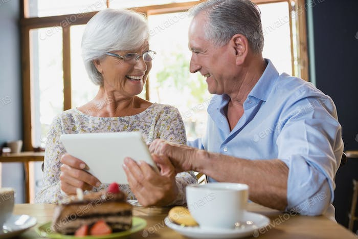 Happy senior couple using digital tablet