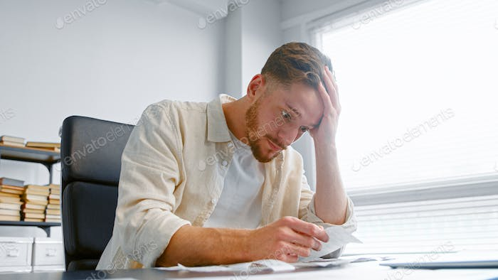 Young man bank accountant with beard looks at paper checks and puts hand on head