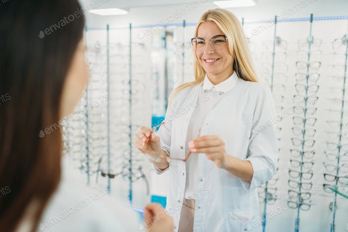 Female optician and customer shooses glasses