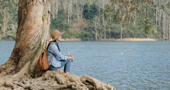 Woman sit on the tree and look at the lake