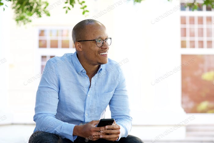 african american businessman sitting outside with mobile phone