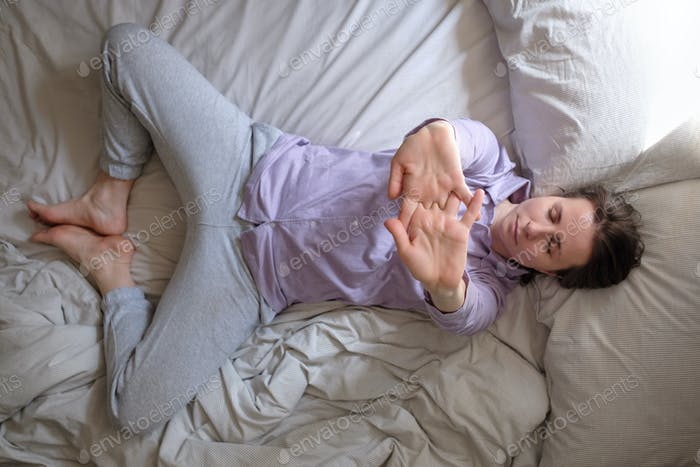 woman doing supta baddha konasana on bed in the morning warming up