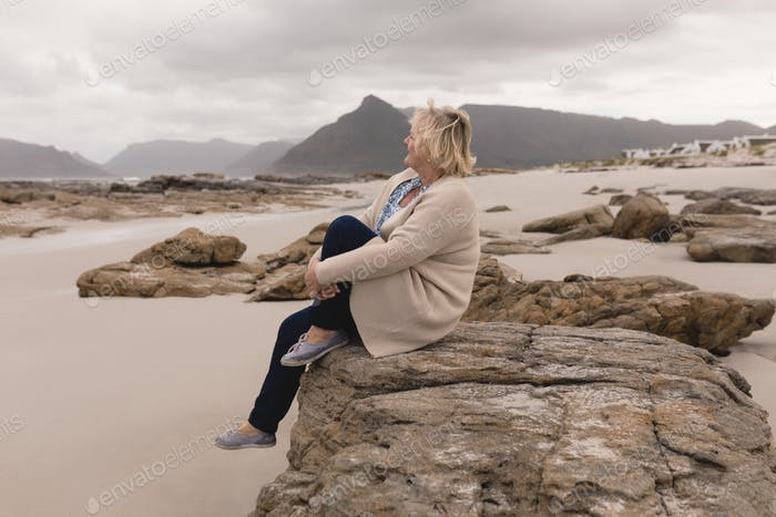 Side view of active senior woman relaxing on the rock at beach
