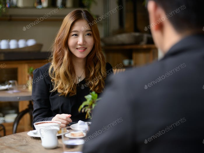 Happy young Asian business couple talking together at the coffee shop