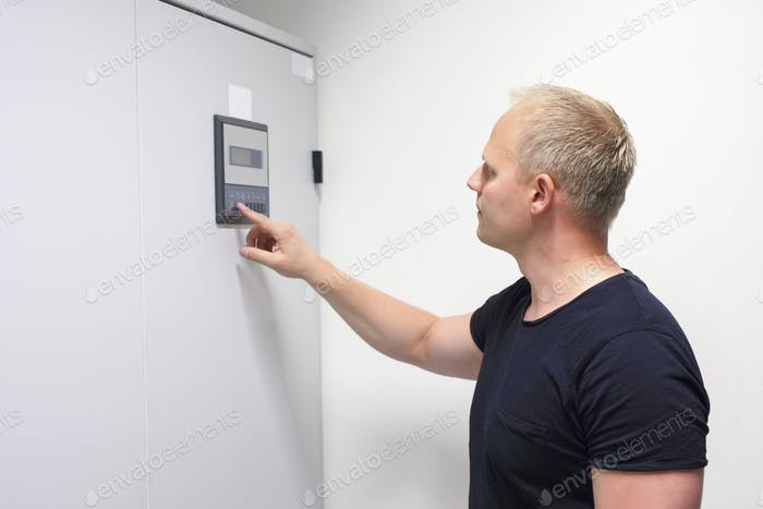 Male Computer Engineer Adjusting Air Conditioner In Datacenter