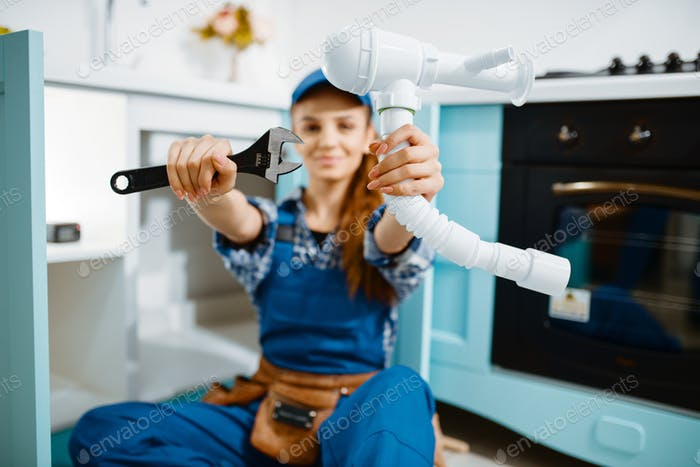 Young female plumber shows wrench and pipe