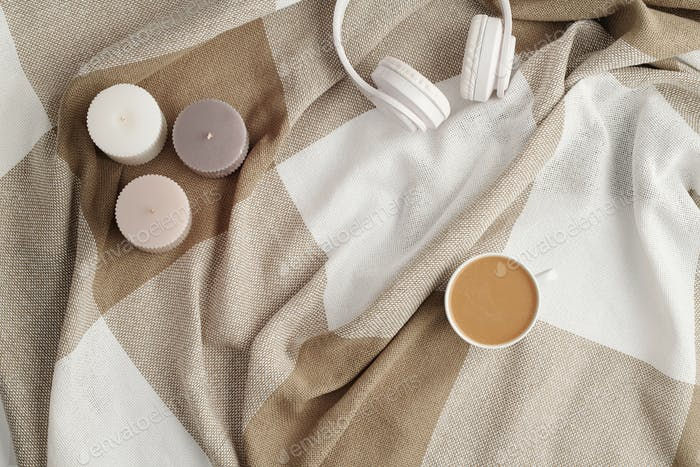 Flat lay of three candles, white headphones and cup of fresh cappuccino