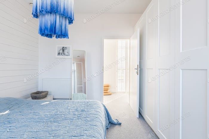 Stylish modern white and blue chandelier in trendy spacious bedroom with king size bed