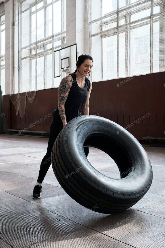 Athletic tattooed Caucasian woman in black sportswear flipping heavy tire
