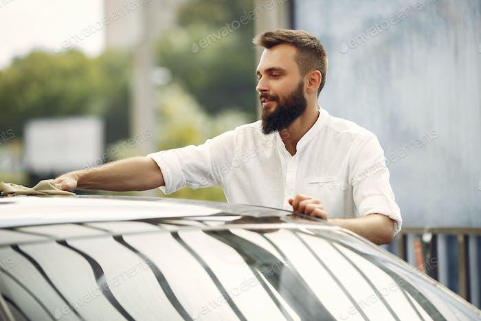 Mann in einem weißen Hemd wischt ein Auto in einer Autowaschanlage