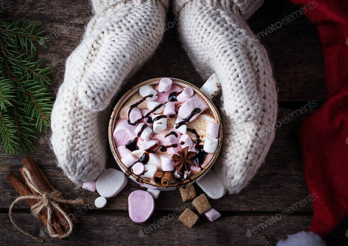 Woman in mittens holding a cup of hot chocolate with marshmallow