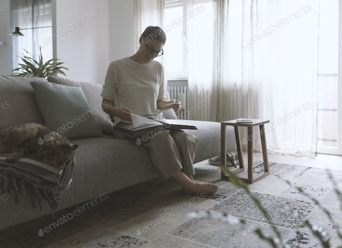 Woman relaxing on the sofa and watching pictures in the photo album
